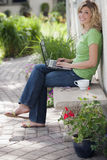 Woman outside with laptop. Smiling young woman relaxing outside using her laptop Royalty Free Stock Photos