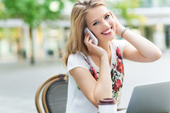 Woman outside a restaurant with a laptop and mobile phone Stock Photo