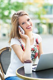 Woman outside a restaurant with a laptop and mobile phone Stock Photos
