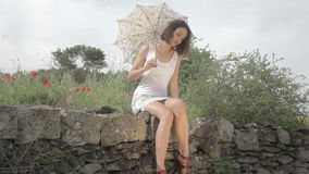 Woman outside rural. A beautiful young woman outdoors in the countryside relaxing with a parasol stock footage