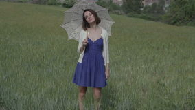 Woman outside rural. A beautiful young woman outdoors in the countryside relaxing with a parasol stock video