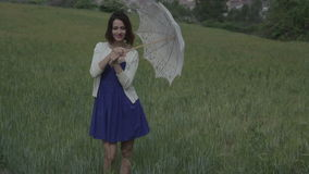 Woman outside rural. A beautiful young woman outdoors in the countryside relaxing with a parasol stock video footage