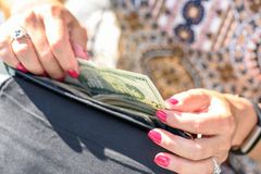 Woman taking cash out of wallet Stock Image
