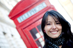 Woman outside a telephone booth Stock Image