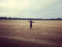 Woman with outstretched arms in field Stock Photo
