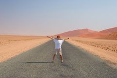 Woman with outstretched arms standing on gravel road crossing the Namib desert, in the Namib Naukluft National Park, main travel d