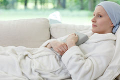 Woman with cancer on sofa. Woman with ovarian cancer lying on sofa holding book in hospice Stock Photography