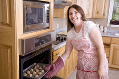 Woman by oven with cookies Royalty Free Stock Photo