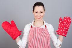 Woman with oven mittens. Funny housewife woman with oven mittens and red apron  on gray background Royalty Free Stock Images