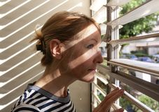 Woman stares out the window through the blinds royalty free stock photos