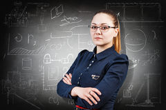 Woman over school chalk board background. Young serious girl over school chalk board background Royalty Free Stock Images