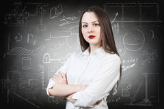 Woman over school chalk board background. Young serious girl over school chalk board background Royalty Free Stock Photo
