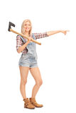 Woman in overalls holding an axe Stock Image