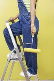 Woman In Overalls Holding Roller Paint Royalty Free Stock Image