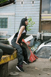 Woman in overalls sits near a warehouse of scrap and wheels Stock Photography