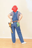 Woman in Overalls and Toolbelt. Woman wearing overalls and toolbelt staring at blank wall Stock Image