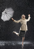 Woman In Overcoat With Umbrella Enjoying The Rain. Full length of a young businesswoman in overcoat with umbrella enjoying the rain royalty free stock images
