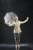 Woman In Overcoat With Umbrella Enjoying The Rain. Full length of a young businesswoman in overcoat with umbrella singing in the rain Royalty Free Stock Photo