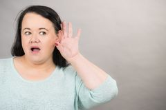 Woman overhearing listening to rumors. Gossip, rumors and hearing concept. Adult plus size woman round face putting hand to her ear to hear better stock photography