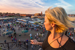 Woman overlooking Jamaa el Fna market square in sunset, Marrakesh, Morocco, north Africa. Female traveler enjoying view of Jamaa el Fna market square, Marrakesh royalty free stock photography
