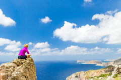 Woman overlooking Mediterranean Sea, Crete Island, Greece. Woman sitting on rocky ledge overlooking Mediterranean Sea on Crete Island, Greece royalty free stock photos