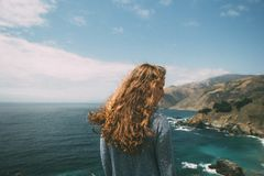 Woman overlooking rocky coastline Stock Photo