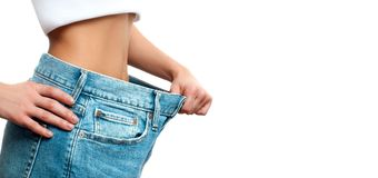 Woman in oversize jeans after weight loss. Woman in oversize jeans after weight loss, diet concept Stock Photo