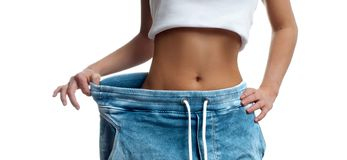 Woman in oversize jeans after weight loss. Woman in oversize jeans after weight loss, diet concept Royalty Free Stock Images