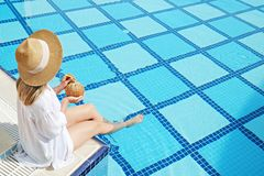 Woman in oversized cotton shirt and straw hat dipping toes in pool. Unrecognizable caucasian woman with fit body wearing blue broad brim straw hat covering her royalty free stock photography