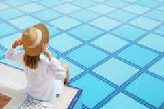 Woman in oversized cotton shirt and straw hat dipping toes in pool. Unrecognizable caucasian woman with fit body wearing blue broad brim straw hat covering her royalty free stock images
