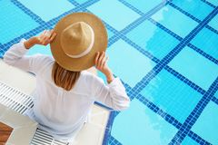 Woman in oversized cotton shirt and straw hat dipping toes in pool. Unrecognizable caucasian woman with fit body wearing blue broad brim straw hat covering her stock image