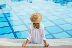 Woman in oversized cotton shirt and straw hat dipping toes in pool. Unrecognizable caucasian woman with fit body wearing blue broad brim straw hat covering her royalty free stock photo