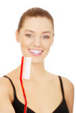 Woman with oversized toothbrush. Royalty Free Stock Image