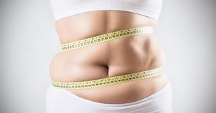 Overweight woman measuring her fat belly. Woman with overweight measuring her fat belly. Obesity concept Royalty Free Stock Images
