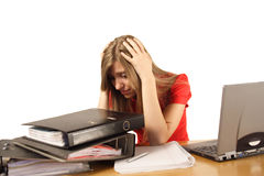 Woman overwhelmed at work. A view of an overwhelmed and desperate woman, holding her head with her hands as she sits at a table, facing a pile of work in large Stock Photography