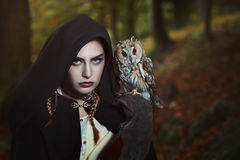 Woman with owl on her shoulder Stock Photography