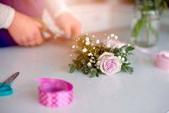 Woman owner of florist shop preparing bouquet of pink roses Royalty Free Stock Photos