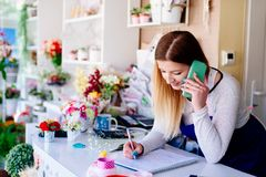 Woman owner of florist shop taking orders. By phone stock photography