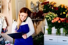 Woman owner of florist shop taking orders Royalty Free Stock Images