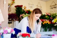 Woman owner of florist shop taking orders Royalty Free Stock Photos