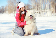 Woman owner hugging white Samoyed dog on snow in winter Stock Photo