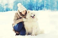 Woman owner hugging white Samoyed dog in winter Stock Photo