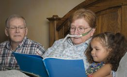 Woman on oxygen reads with family stock image
