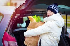 Woman with package of food opened trunk of car in parking lot of supermarket. Shopping by car. Put shopping in trunk of car. Girl with paper product package Royalty Free Stock Photos