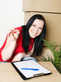 Woman with package holding keys to new apartment Stock Photos