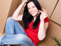 Woman with package holding keys to new apartment Stock Photo