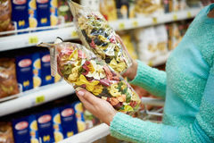 Woman with package pasta in shop Stock Images