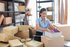 Woman packed some stuff to be shipped. Young woman packing of clothes on the boxes to be shipped in her office stock photo