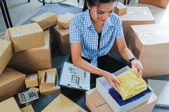 Woman packed some stuff to be shipped. Young woman packing of clothes on the boxes to be shipped in her office royalty free stock image