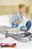 Woman With Packed Suitcase On Bed. Woman sitting cross legged on bed next to folded clothes and packed suitcase Royalty Free Stock Photo